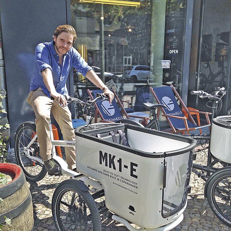 Daniel Brühl beim Probesitzen auf einem Lastenrad der Marke Butchers & Bicycles.